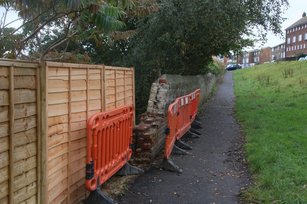 Collapsing wall with orange safety fencing.