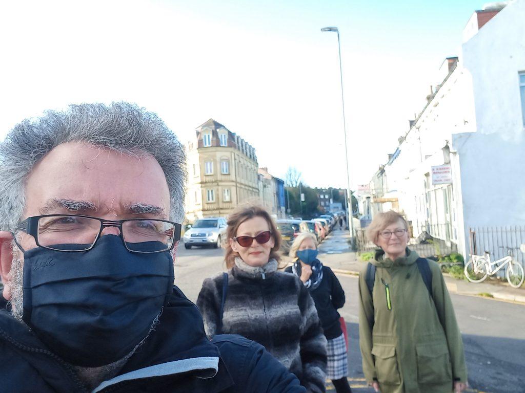 Four people (one man, three women) in socially-distanced selfie