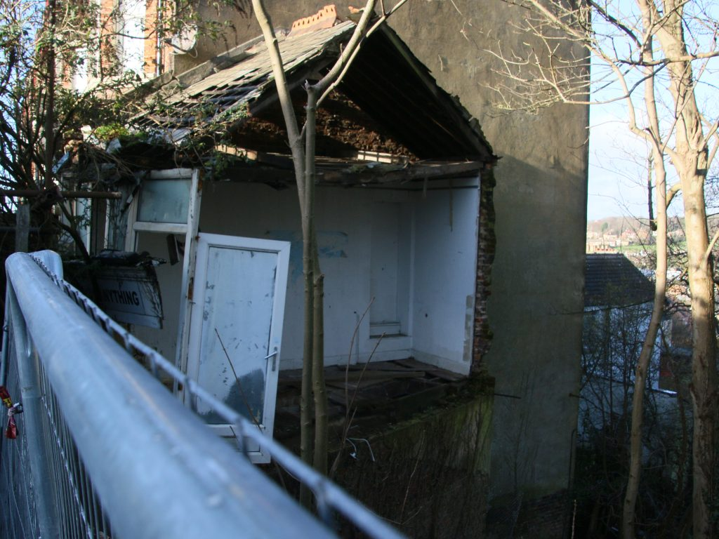 Remains of demolished shop, showing a door, window, and part of a roof, behind a fence