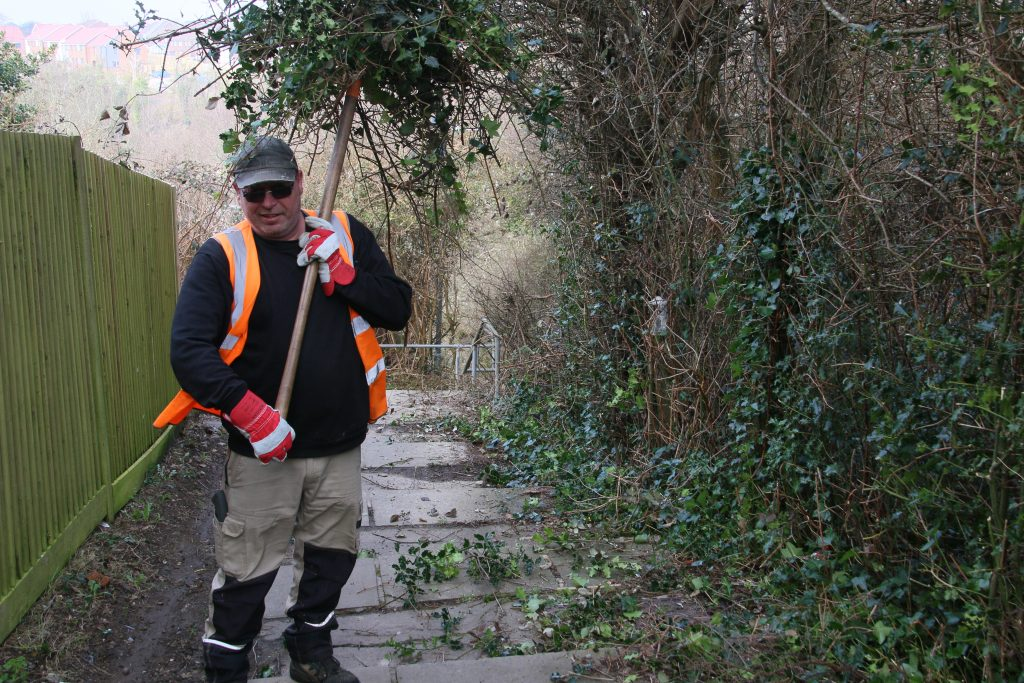 Man in hi-viz with cut shrubbery from steps