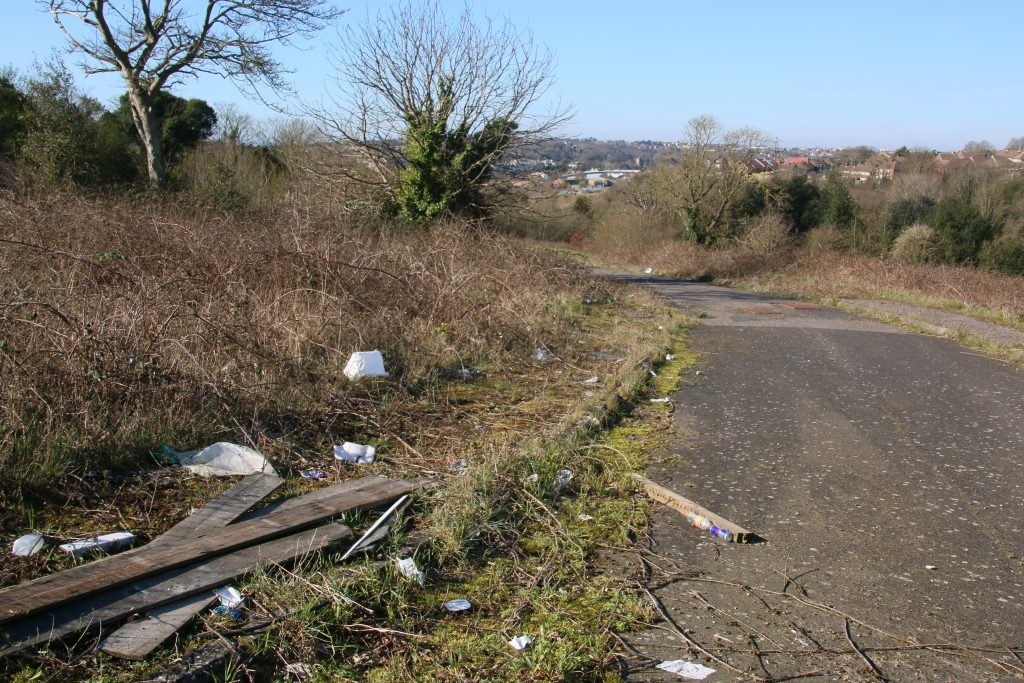 View of road across wasteland with litter and flytips