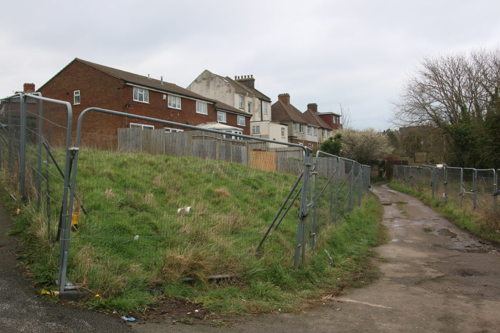 Development site on Clifton Road - untidy area of land surrounded by Herras fencing, with unmade road between two halves.