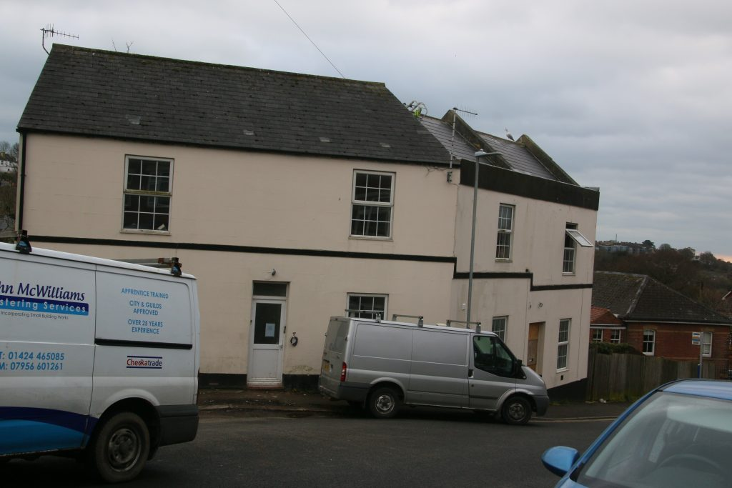 Former care home, large L-shaped house with cream rendering, with builder's vans outside.