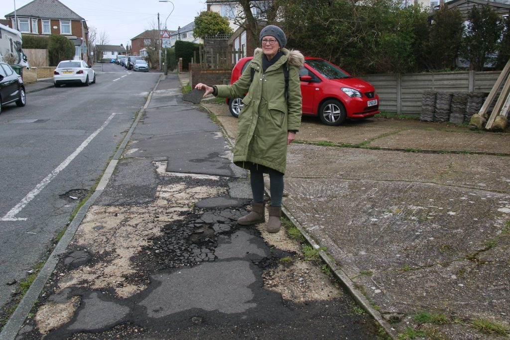 Ruby Cox holding a lump of tarmac from damaged footway