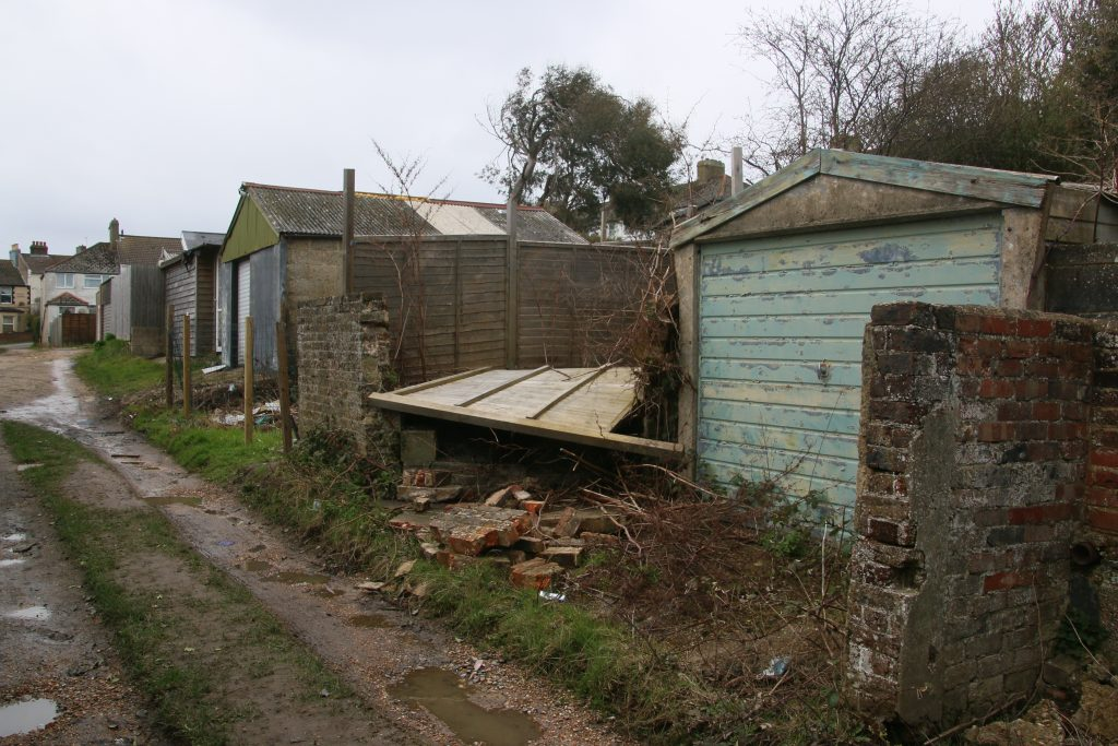 Untidy garages and broken wall on unmade road