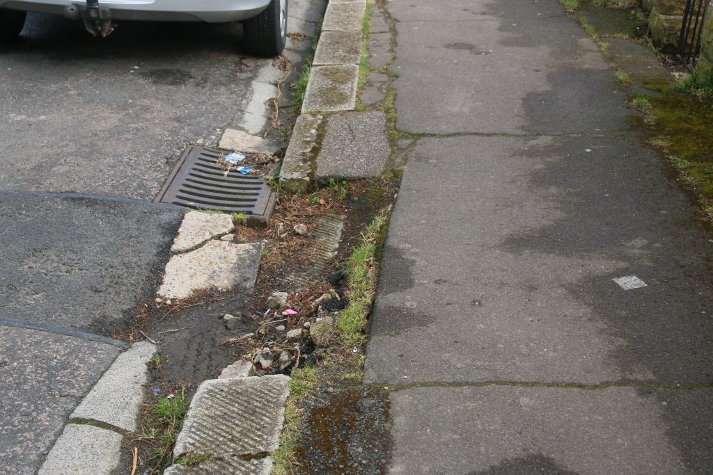 Missing kerbstone and damaged footway