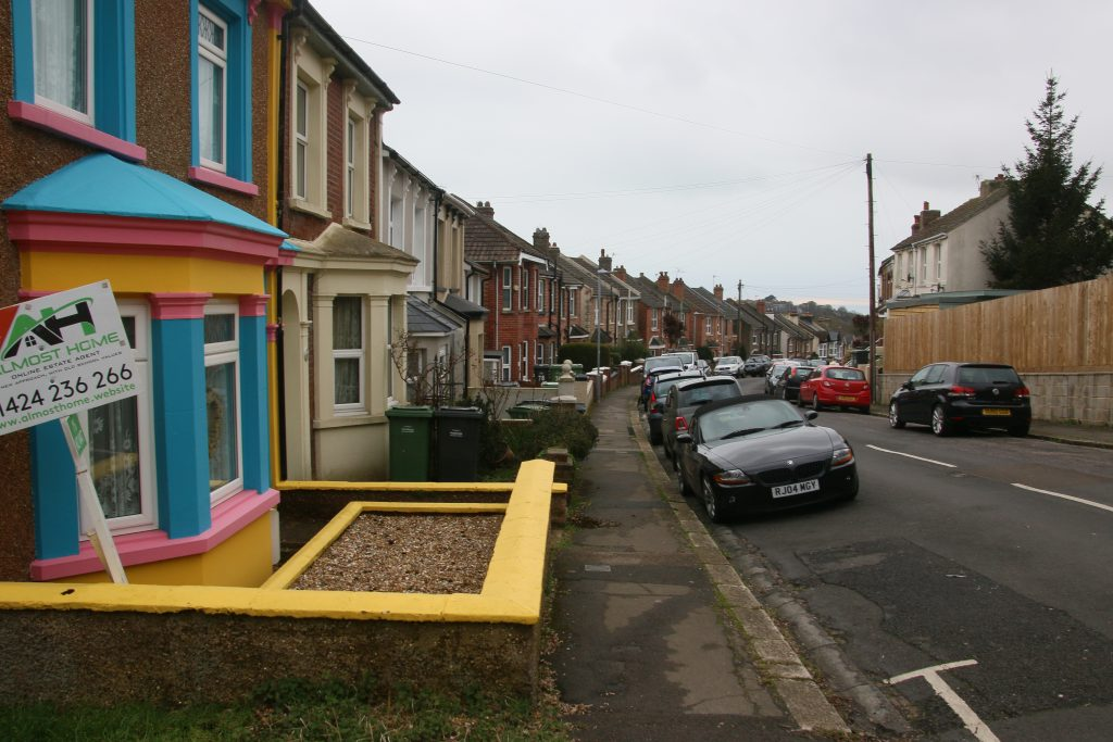 View along Clifton Road, with yellow and blue house