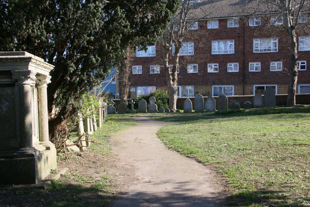 Halton Graveyard - path across grassed area with gravestones along the edge.