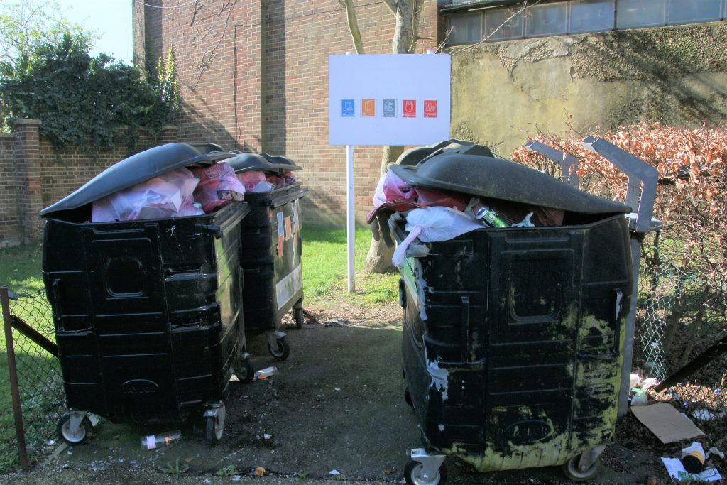 Overflowing communal recycling bins, two bins facing another two bins