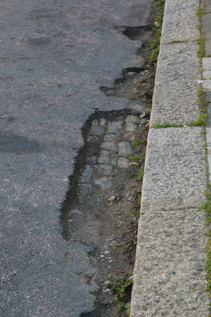 Damaged tarmac with cobbles beneath exposed