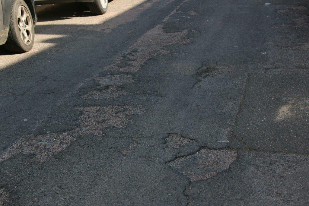 damaged tarmac road surface