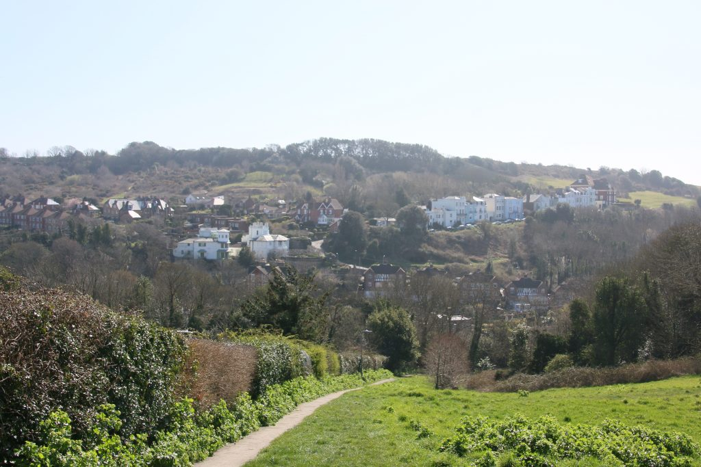 Path sloping down hillside, view across to Hastings Country Park