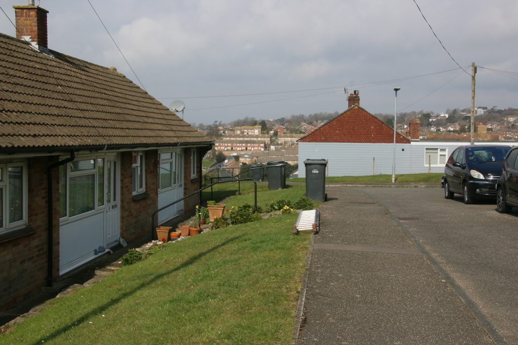 High Bank - bungalows with grass verge in front, view over Hastings