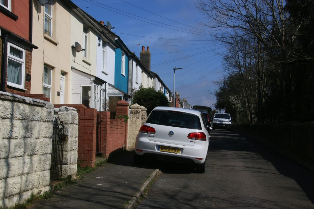 Narrow residentia road with van squeezing past parked cars