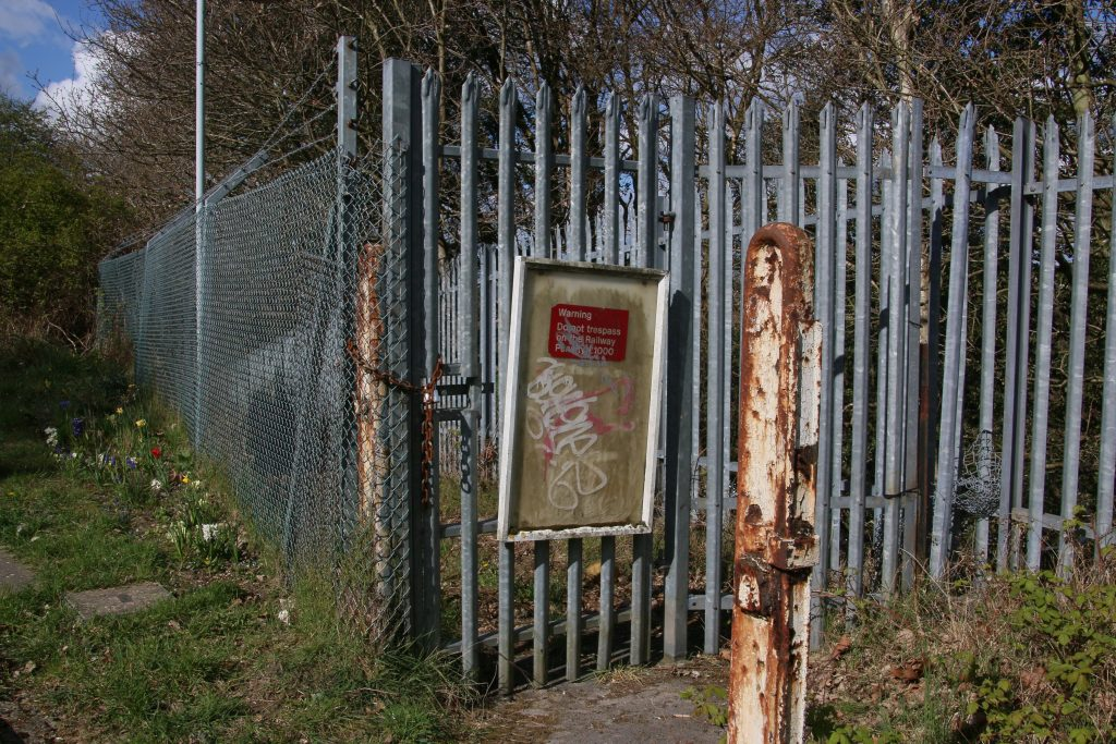 Rusty spiked railings closing off the entrance to a footpath, old illegible sign on the gate