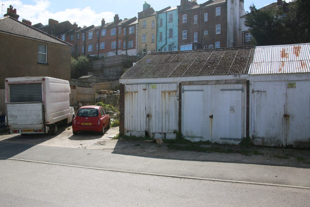 Disused garages on small plot of unused land with parked car and van